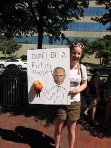 Young woman holding handmade sign saying 'Don't be a Putin puppet'