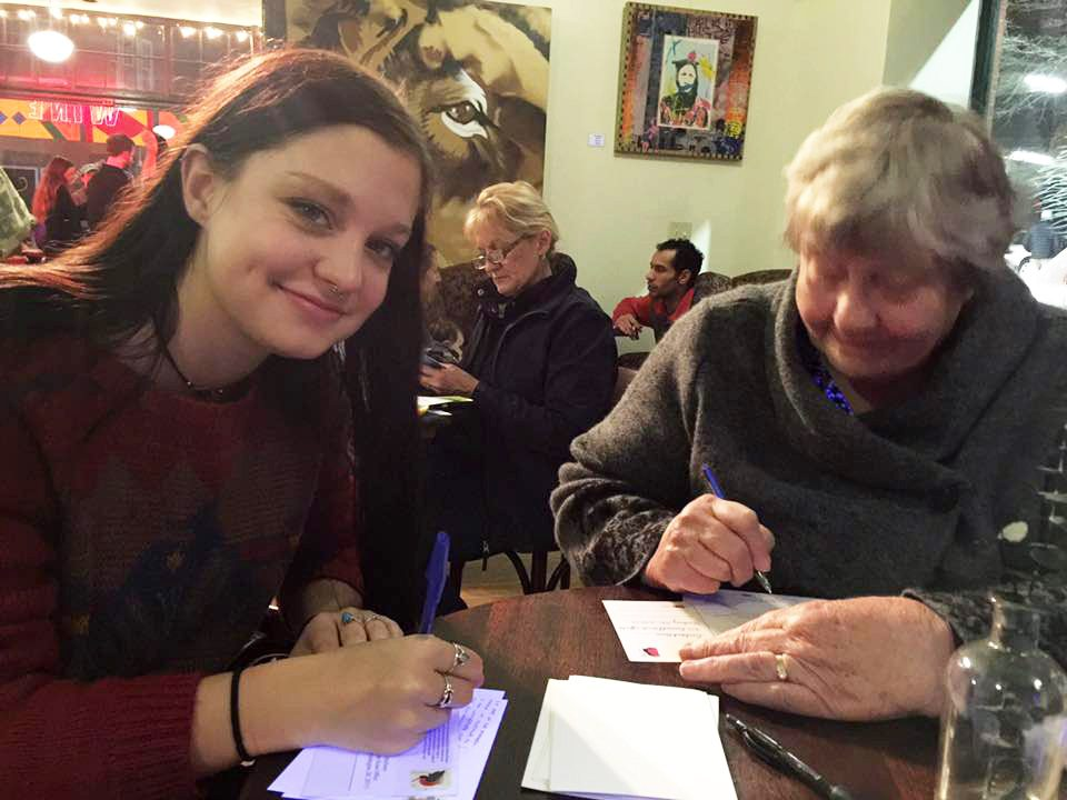 Indivisible Asheville members in coffee shop writing letters to their Members of Congress