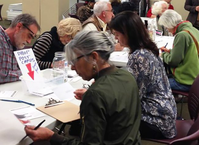 Photo of adults at a table writing postcards to their members of Congress