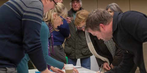 Photo of people at January Indivisible Asheville meeting signing up for get-out-the-vote efforts