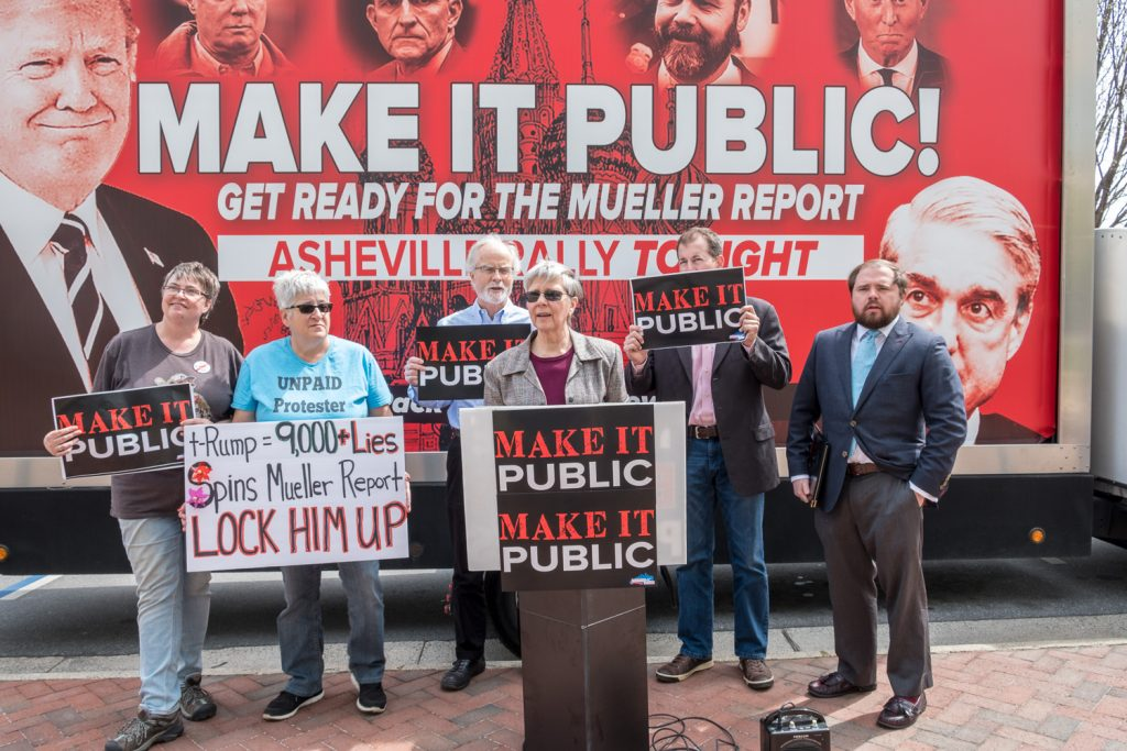 "Indivisible AVL representative addresses local media at April 4 Press Conference, flanked by local activists, standing in front of a large billboard that says ""Make It Public: Get Ready for the Mueller Report"""
