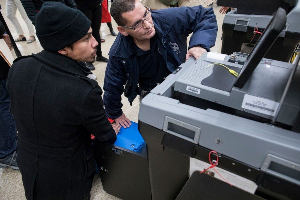 Photo of technicians trying to repair a voting machine at a polling location on November 8, 2016