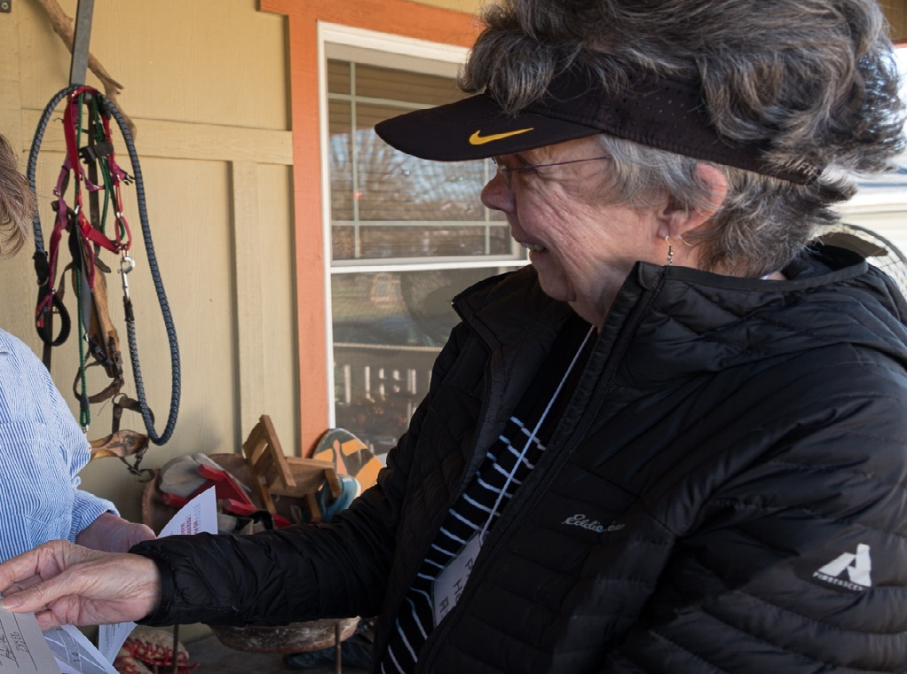 Photo of a volunteer non-partisan canvasser at the door talking with a voter
