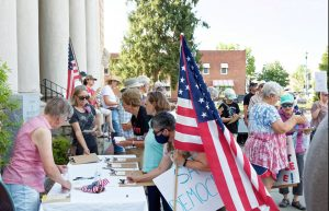 Photo of democracy supporters in front of Henderson County Historic Courthouse holding flags and filling our postcards to North Carolina Senators Tillis and Burr, urging them to support the For the People Act