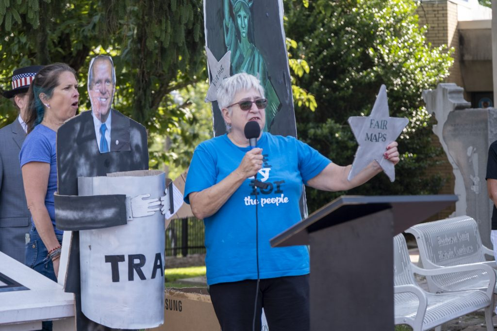 Activist speaking at outdoor rally, holding a large star labeled Fair Maps. with lifesize image of Senator Thom Tillis holding a trash can standing behind her